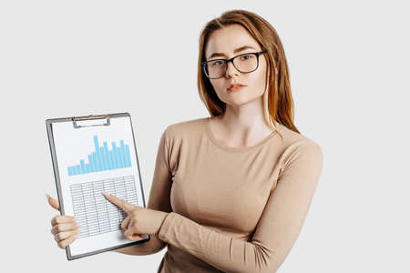 Beautiful young business woman wearing glasses isolated on gray background. Achieving career wealth business concept. Mockup copy space. Hold a clipboard with documents charts and reports