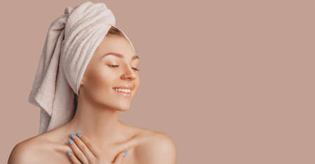 Beautiful sensual young girl with clean skin on a beige background with a mockup. Topless woman in a towel. The concept of spa treatments, natural beauty and care, youth, cream and mask, freshness