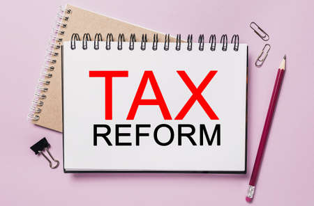 Text tax reform on a white sticker with office stationery background. Flat lay on business, finance and development concept