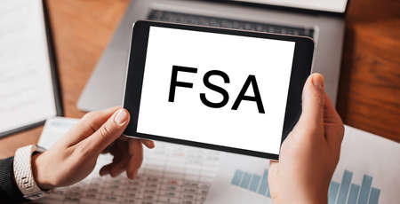 Man hands holding tablet with text FSA at workplace. Businessman working at desk with documents 版權商用圖片