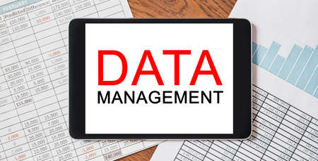 Tablet with text DATA MANAGEMENT on your desktop with documents, reports and graphs. Business and finance concept