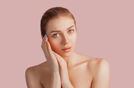 Beautiful sensual young girl with clean skin on a pink background with a mockup. Topless woman in a towel. The concept of spa treatments, natural beauty and care, youth, cream and mask, freshness