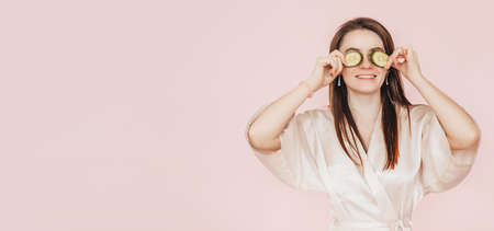 Girl make homemade face beauty masks. Cucumbers for the freshness of the skin around the eyes. Woman take care of youthful skin. Model laughing and having fun in spa on pink background