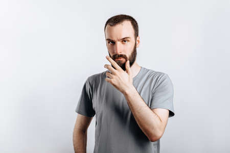 Serious puzzled handsome male model with beard holding hand on chin as if thinking about something, squinting at camera with suspicious look and standing over gray background. Man decides what to buy