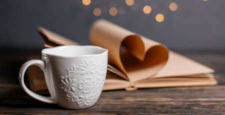 Heart made from book sheets with a cup, love and valentine concept on a wooden table
