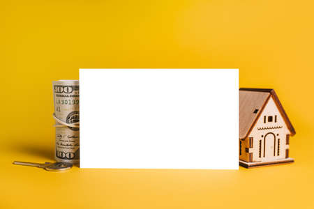 House miniature model and money with blank background on a yellow background. Investment, real estate, home, housing