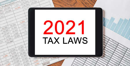 Tablet with text 2021 tax laws on your desktop with documents, reports and graphs. Business and finance concept