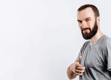 Portrait of cheerful young handsome man smiling looking at camera pointing finger forward on white background with space for advertising mock up 版權商用圖片