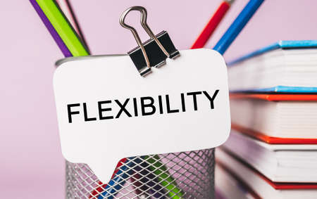 Text Flexibility a white sticker with office stationery background. Flat lay on business, finance and development concept