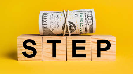 STEP with money on a yellow background. The concept of business, finance, credit, income, savings, investments, exchange, tax
