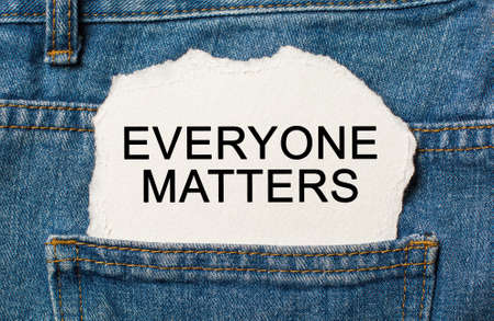 Everyone Matters on torn paper background on jeans business and finance concept