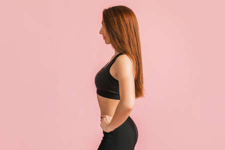 Fitness girl smiling in black sportswear on a pink background. Slim woman with a beautiful athletic body and tanned skin
