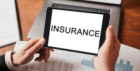 Man hands holding tablet with text INSURANCE at workplace. Businessman working at desk with documents