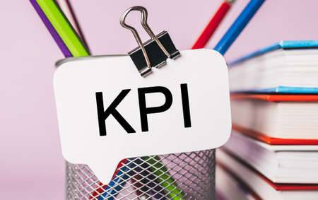 Text KPI on a white sticker with office stationery background. Flat lay on business, finance and development concept