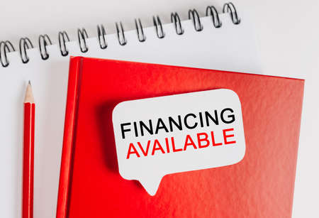 Text Financing Available on a white sticker with office stationery background. Flat lay on business, finance and development concept