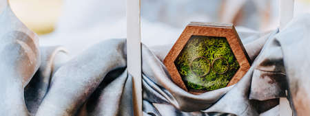 Two wedding rings in a wooden box with a plant moss on a purple fabric background