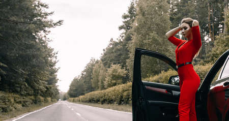 A beautiful young girl in a red overalls stands by a black car on an empty road in the forest