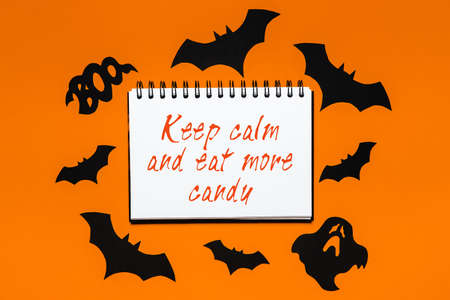 Happy halloween holiday concept. Notepad with text Keep calm and eat more candy on white and orange background with bats, pumpkins and ghosts