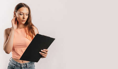 Girl student frowns with displeasure and reads information in documents. Beautiful young business woman holds a clipboard with mockup on gray background. Study and business concept. Online learning