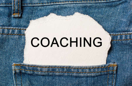 COACHING on torn paper background on jeans study and education concept