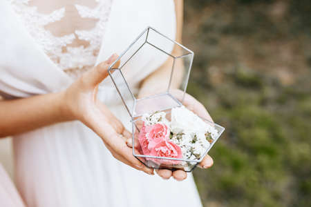 Bride holding wedding box for rings with white and pink flowers
