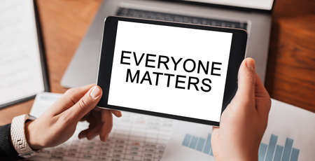 Man hands holding tablet with text Everyone Matters at workplace. Businessman working at desk with documents 版權商用圖片