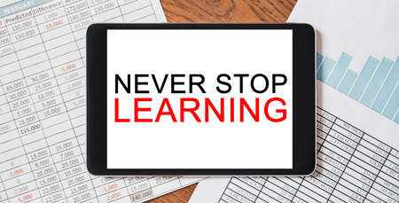 Tablet with text Never Stop Learning on your desktop with documents, reports and graphs. Business and finance concept 版權商用圖片