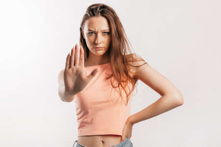 Stop. Enough. Young beautiful girl stretches out her hand to the camera to stop the effect. Woman with fashion orange top on an isolated gray background. Bad events, despair and threat
