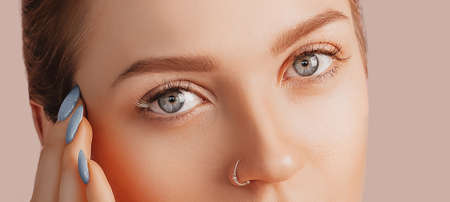 Beautiful sensual young girl with clean skin. Female eyes close-up shot. Woman looking at the camera. The concept of spa treatments, natural beauty and care, youth, cream and mask, freshness