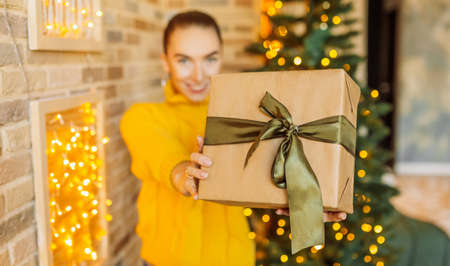 Beautiful cheerful happy young girl with christmas gifts on the background of a new year tree at home