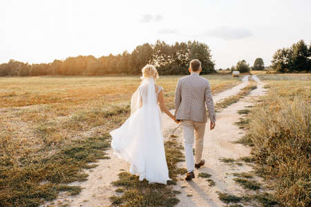 Bride and groom on wedding day hug and walking along the road to the forest at sunset