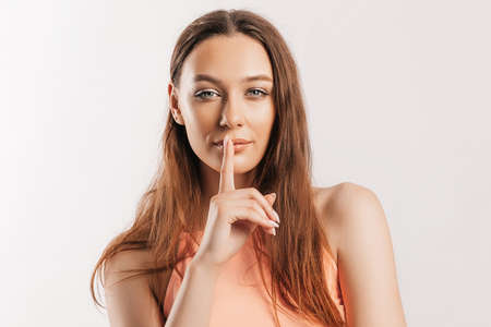 Shh gesture. Young beautiful serious girl holding a finger to her lips on a white isolated background. A woman asks to be silent, a place for advertising. Positive brunette in orange top
