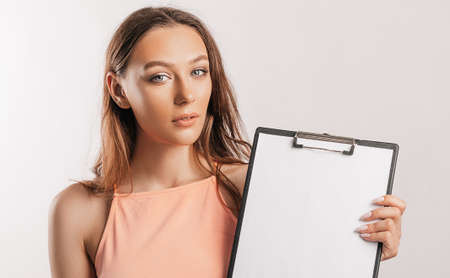 Girl student points to the sheet. Beautiful young business woman holds a clipboard with mockup blank space isolated on gray background. Study and business concept. Online learning cover