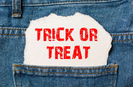 Trick or Treat on white paper in the pocket of blue denim jeans