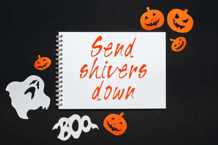Happy halloween holiday concept. Notepad with text Send shivers down on black background with bats, pumpkins and ghosts 版權商用圖片