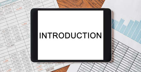 Tablet with text Introduction on your desktop with documents, reports and graphs. Business and finance concept