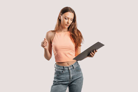 Girl student writes information. Beautiful young business woman isolated on gray background. Achieving career wealth business concept. Mockup copy space. Hold a clipboard with documents 版權商用圖片