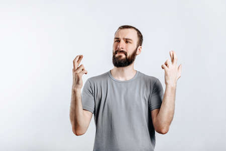 Handsome young man frown and cross fingers in hope on white background with space for advertising mock up