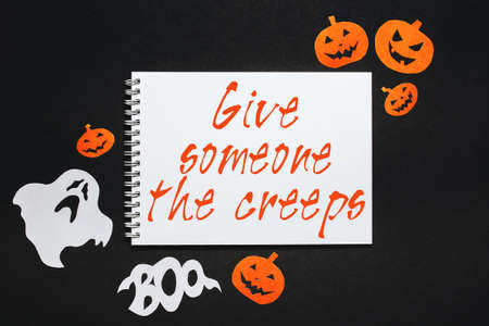 Happy halloween holiday concept. Notepad with text Give someone the creeps on black background with bats, pumpkins and ghosts