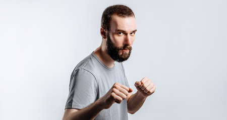 Portrait of handsome young man frowning while looking at camera holding fists and boxing on white background with space for advertisement mock up