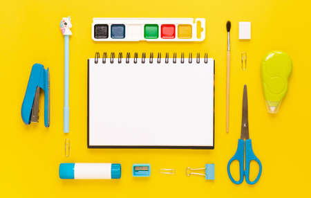 Top view of modern white, blue, yellow office desktop with school supplies and stationery on table around empty space for text. Back to school concept flat lay with mockup 版權商用圖片