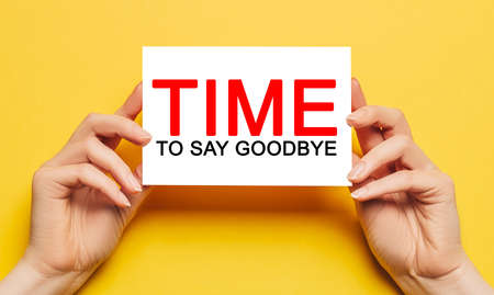 Female hands hold card paper with text Time to Say Goodbye on a yellow background. Business and finance concept 版權商用圖片