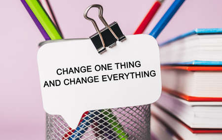 Text Change one thing and change everything on a white sticker with office stationery background. Flat lay on business, finance and development concept