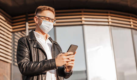 Handsome man in a protective mask on his face with glasses with a smartphone on the street of a big city. Businessman talking on the phone on urban background 版權商用圖片