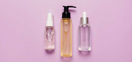 Organic cosmetics packaging design. Flat lay, top view clear glass pump bottle, brush jar, moisturizing serum jar on a purple background. Natural cosmetics SPA
