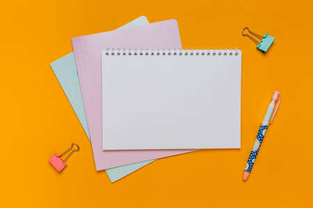 Notepad, exercise book and pen on the desk. Mock up in copy space office on orange background. Back to school