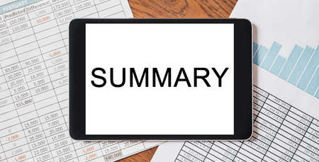 Tablet with text Summary on your desktop with documents, reports and graphs. Business and finance concept