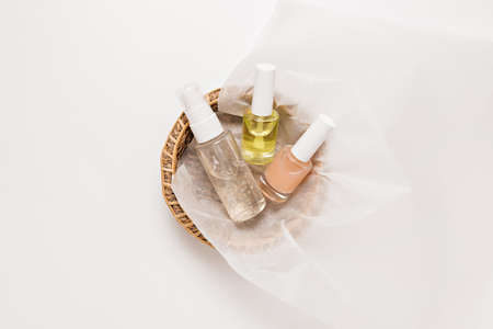 Organic cosmetics packaging design. Flat lay, top view clear glass pump bottle, brush jar, moisturizing serum jar in a paper basket on a white background. Natural cosmetics SPA