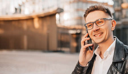 Handsome man with glasses with a smartphone on the street of a big city. Businessman talking on the phone on urban background
