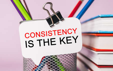 Text Consistency is the key on a white sticker with office stationery background. Flat lay on business, finance and development concept